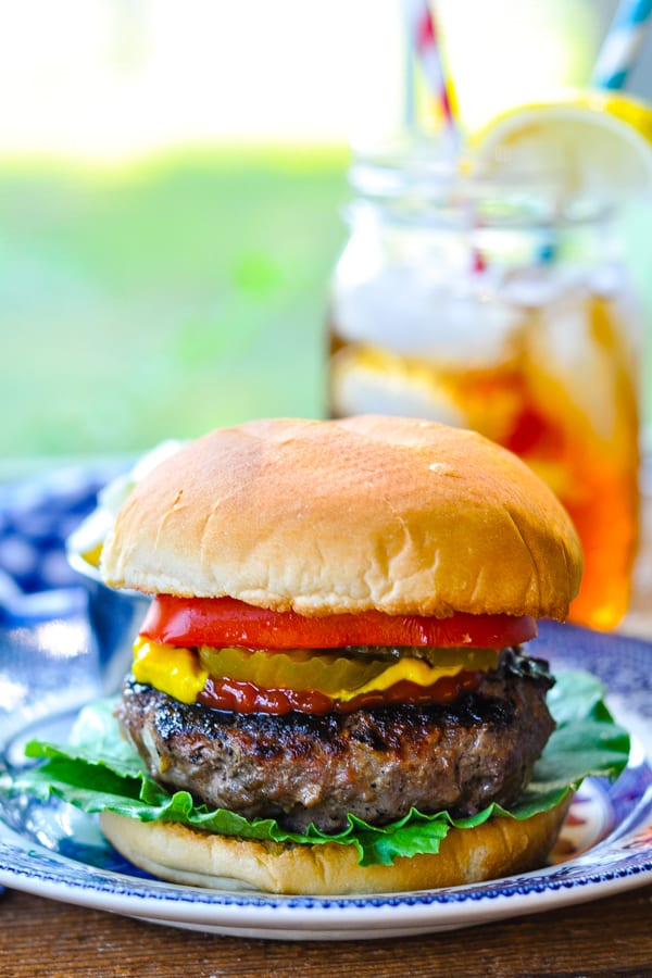 Front shot of a grilled hamburger with lettuce tomato and onion on a blue and white plate