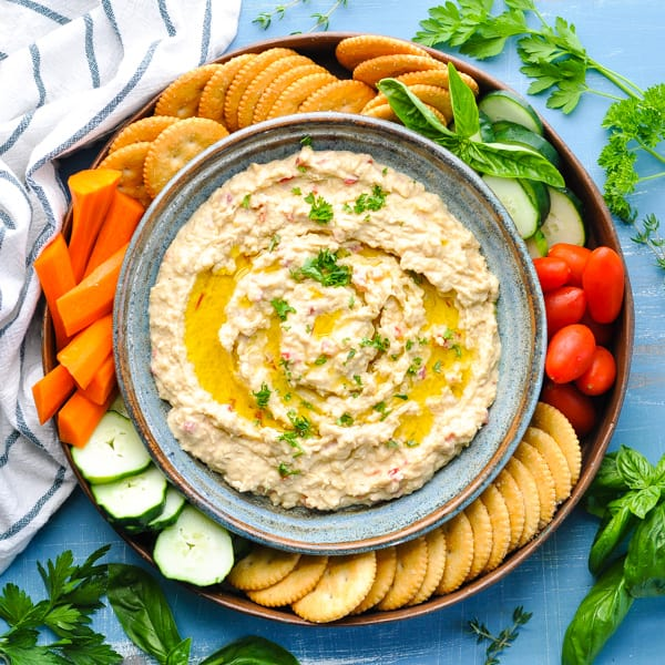 Square shot of a bowl of homemade hummus with dipping snacks