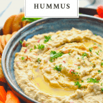 Front shot of a bowl of homemade hummus with a text title in a box at the top of the image
