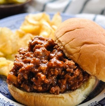Front shot of a homemade sloppy joe sandwich on a blue and white plate