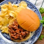 Overhead shot of an open-face sloppy joe on a plate with potato chips