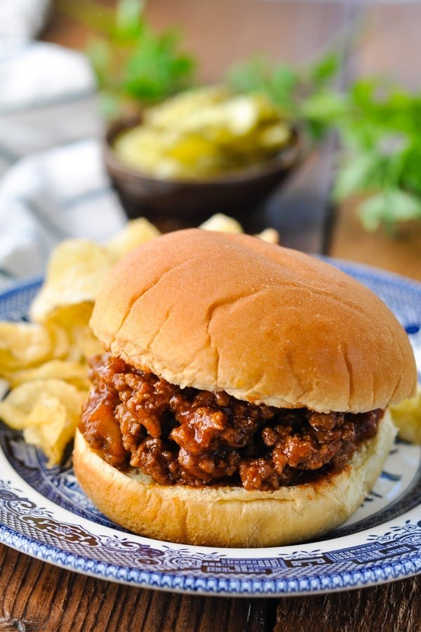 Homemade sloppy joes with ketchup on a hamburger bun and potato chips in the background