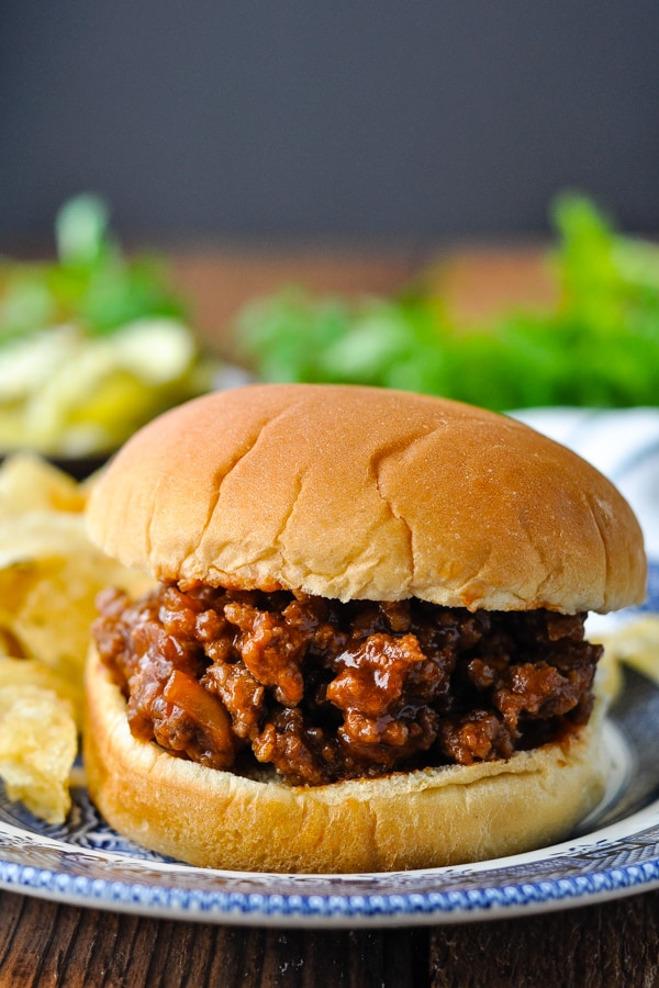 Front shot of homemade sloppy joes on a plate in front of a dark background