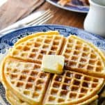 Plate of homemade waffles on a wooden table with bacon in the background
