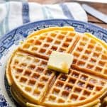 Homemade waffles on a blue and white plate with a striped towel in the background