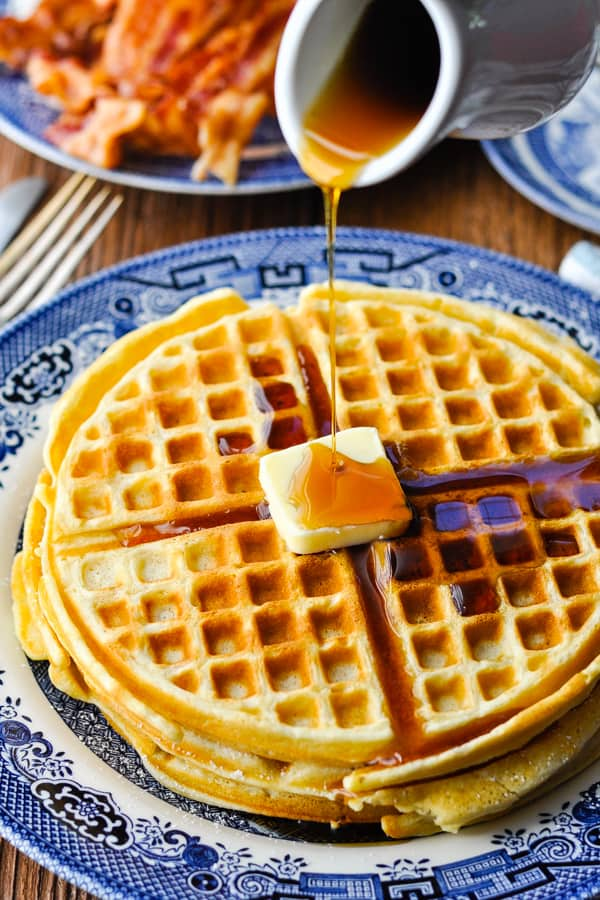 Close up shot of crispy waffles with butter and syrup