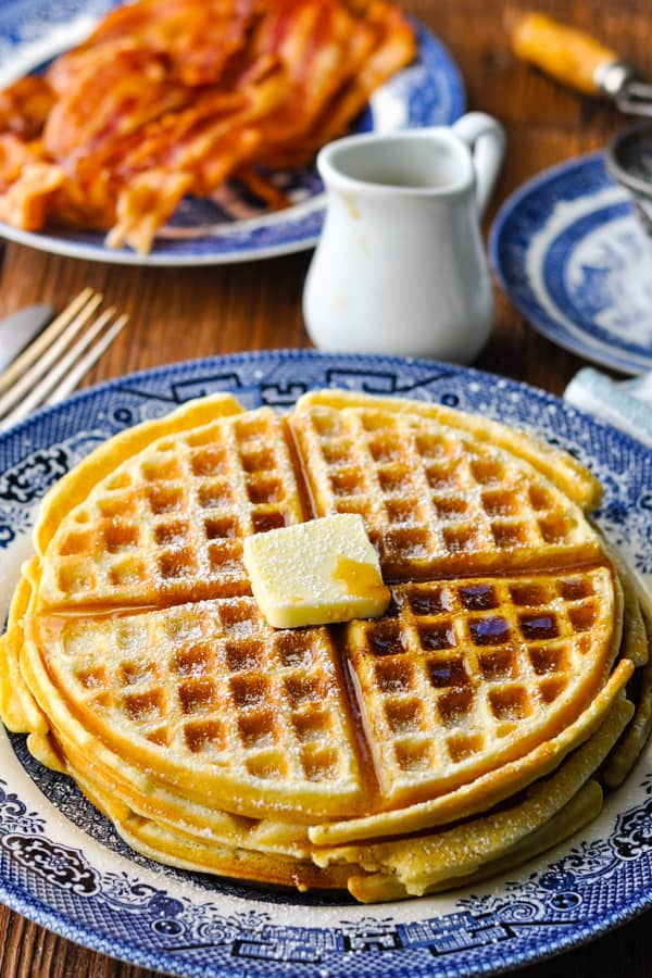 Homemade waffles with butter and syrup on a blue and white plate
