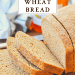 Side shot of a loaf of sliced honey wheat bread with text title at top