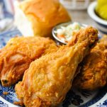Fried chicken drumstick on a plate with coleslaw and biscuits in the background