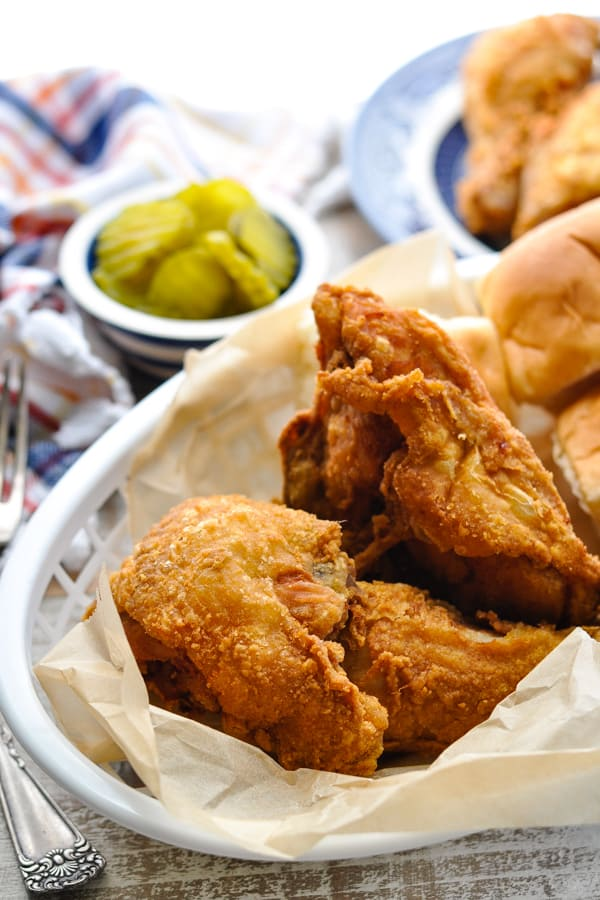 Front shot of a basket of crispy fried chicken with a side of pickles