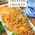 Pecan crusted chicken breasts on a white platter with text title at top