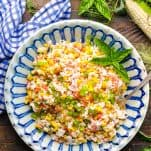 Overhead shot of a bowl of rice salad with corn and pimentos