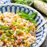 Close up side shot of easy summer rice salad with corn and bacon in a ceramic bowl