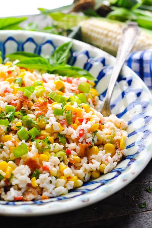 Close up front shot of rice and corn salad in a big bowl with a silver serving spoon