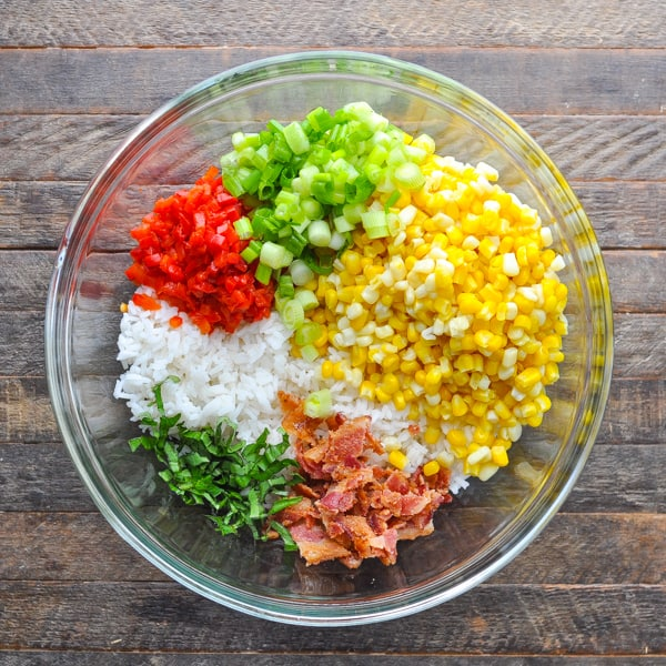 Overhead shot of rice salad ingredients in a large glass mixing bowl
