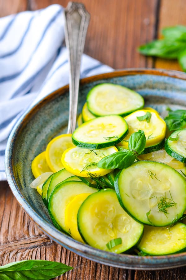Front shot of a bowl of sauteed zucchini with a blue and white striped towel in the background