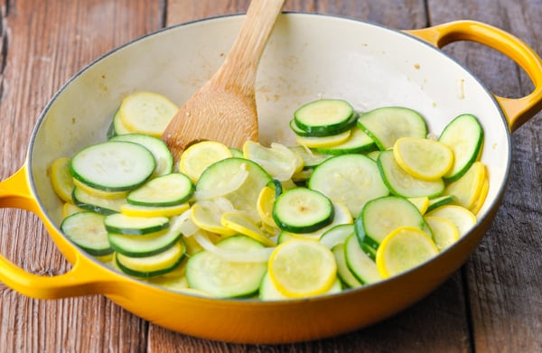 Cooking zucchini and squash on the stovetop in a yellow cast iron skillet