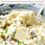 Close up shot of a bowl of skin on mashed red potatoes with text title box at top