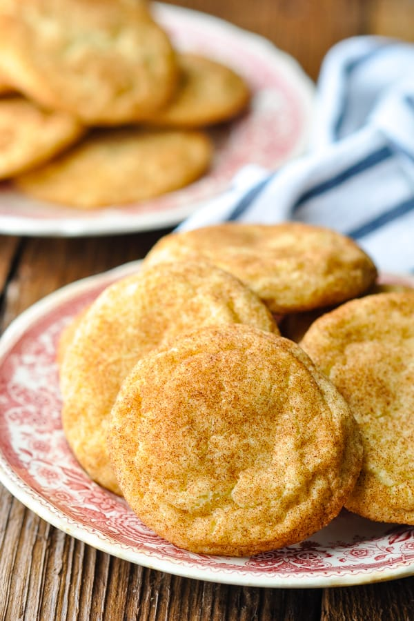 Close up side shot of a plate of snickerdoodles with a blue and white striped towel in the background
