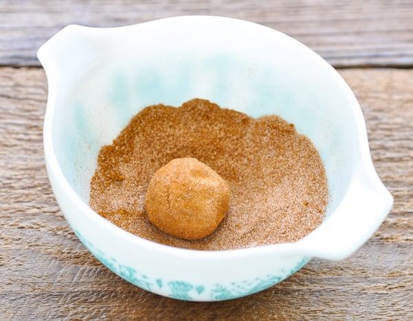 Rolling snickerdoodle cookies in a bowl of cinnamon sugar