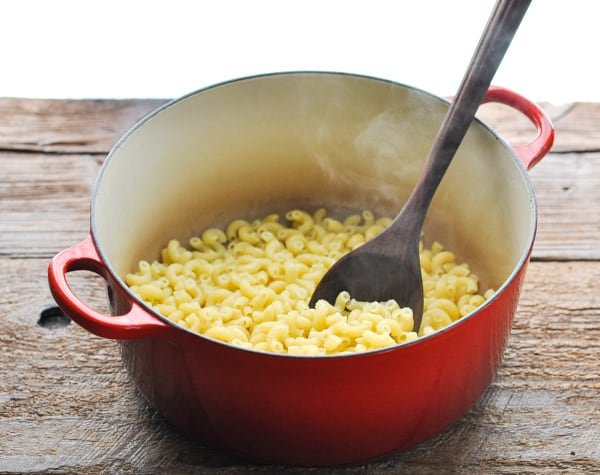 Cooked elbow macaroni in a red Dutch oven