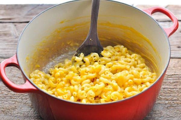 Stirring cheese into elbow macaroni in a large red Dutch oven