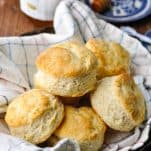 Basket of southern buttermilk biscuits with honey in the background
