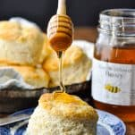 Drizzling honey on top of a buttermilk biscuit