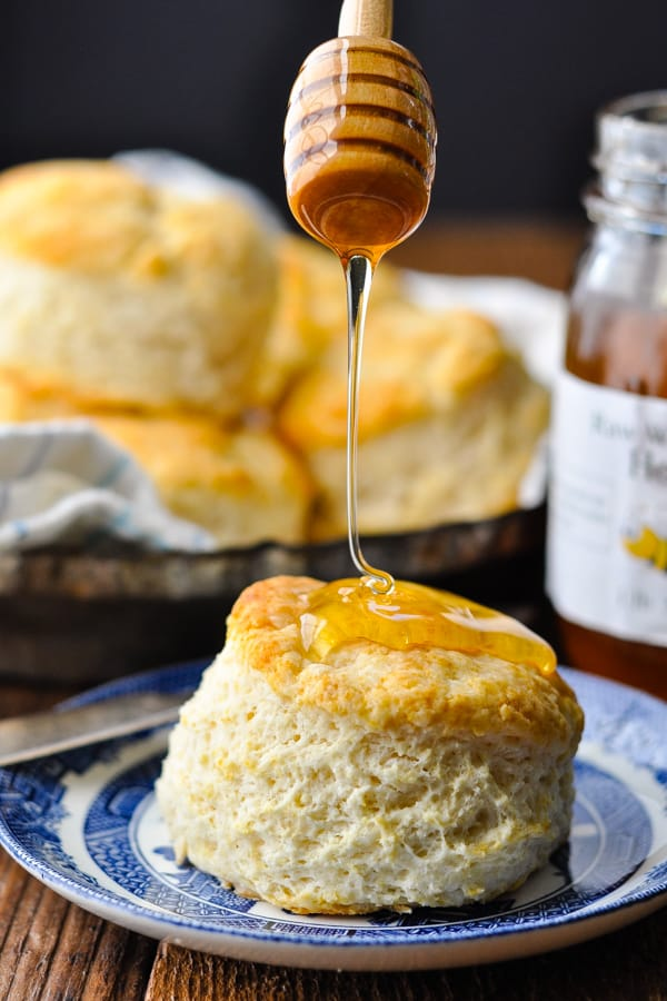 Close up shot of a homemade buttermilk biscuit on a plate with honey on top