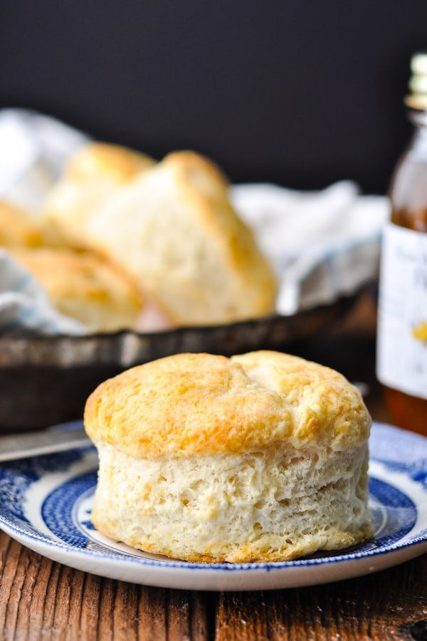 Side shot of a southern buttermilk biscuit on a plate in front of a dark background