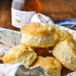 Easy buttermilk biscuits in a basket with a towel and honey in the background