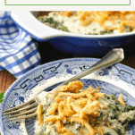 Front shot of a plate of spinach and ground beef casserole with text title at top