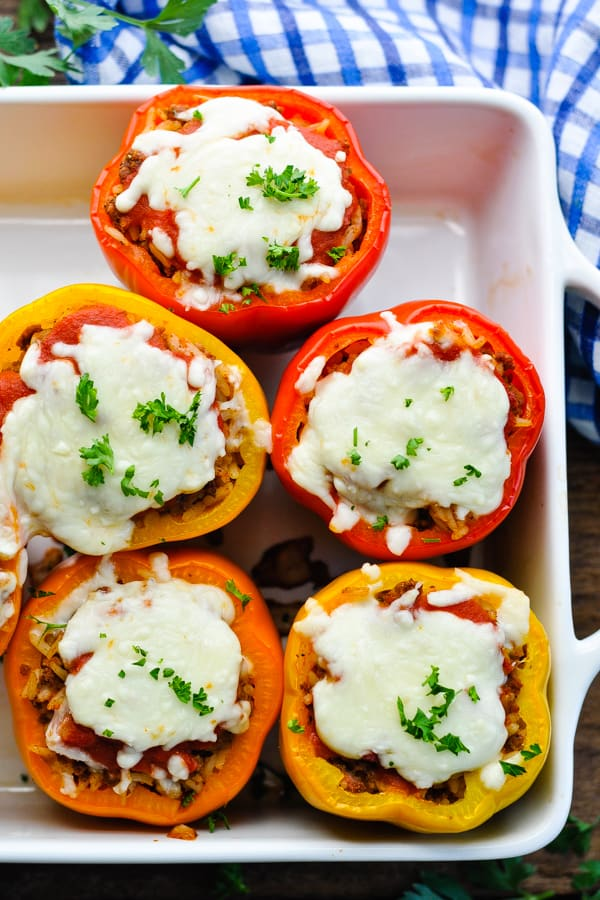 Overhead shot of colorful stuffed peppers with fresh herbs on top