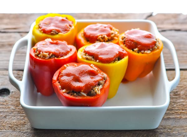 Process shot of assembling stuffed peppers with rice and ground beef
