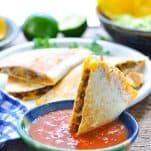 Dipping a taco quesadilla triangle in a bowl of salsa