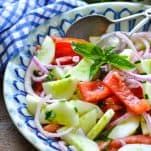 Blue and white ceramic bowl full of tomato cucumber onion salad with silver serving tongs