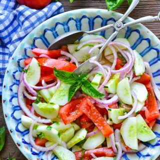 Overhead shot of a bowl of tomato cucumber red onion salad