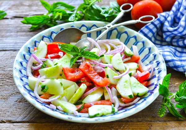 Horizontal side shot of a bowl of tomato cucumber salad with silver serving tongs