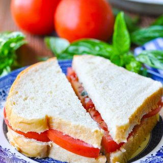 Close up side shot of a tomato sandwich with basil on white bread