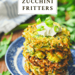 Stack of crispy zucchini fritters on a plate with a text title box at the top of the image
