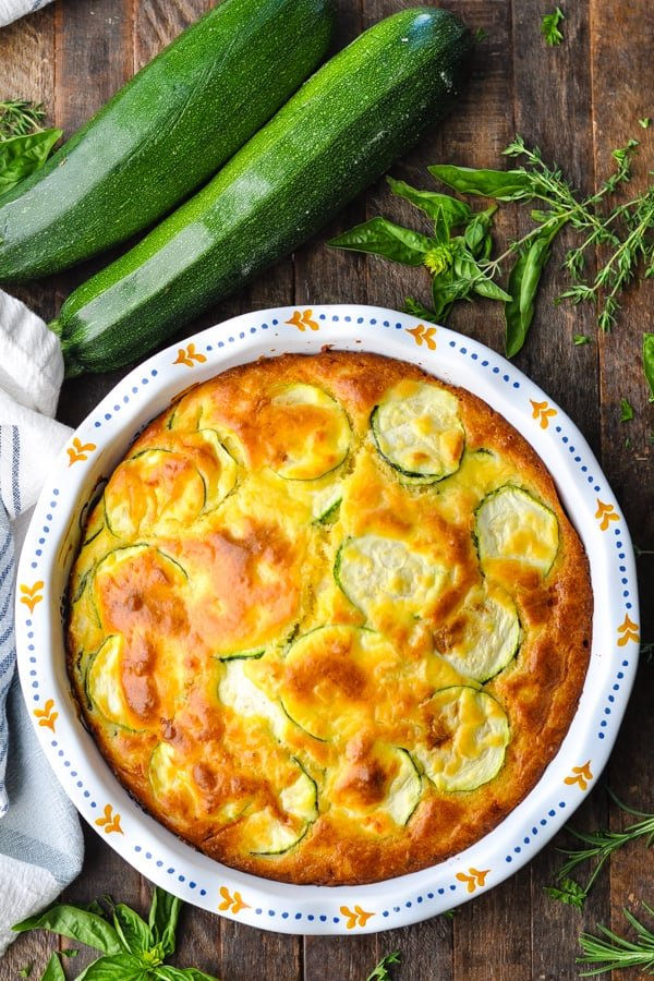 Overhead image of easy zucchini pie on a table surrounded by herbs and fresh zucchini