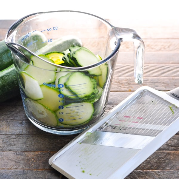Sliced zucchini in a measuring cup with a mandoline slicer nearby