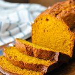 Close up front shot of a sliced loaf of moist pumpkin bread