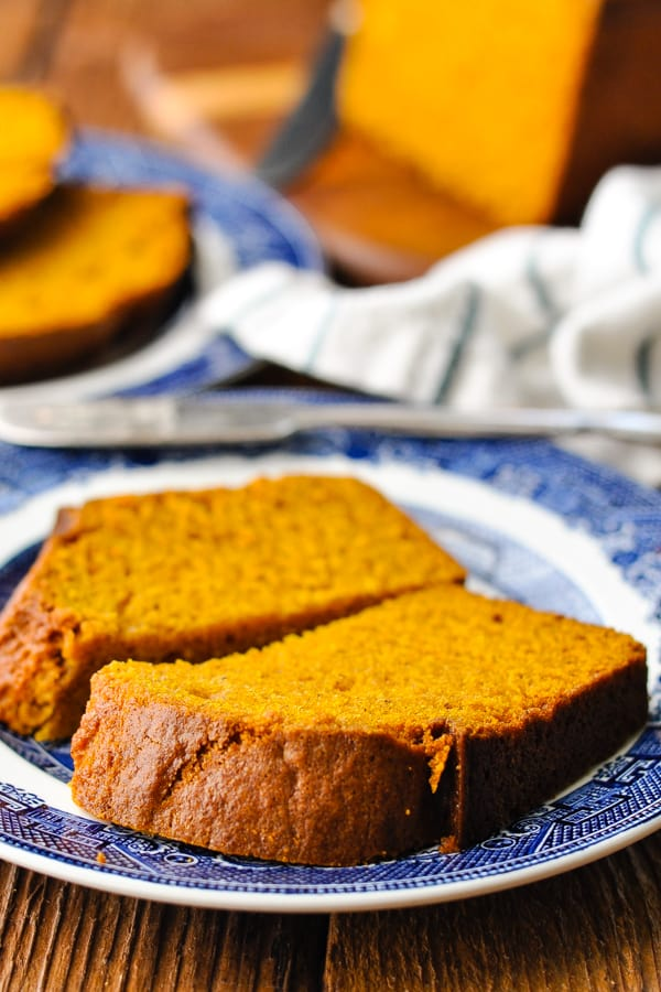 Front shot of a slice of the best pumpkin bread recipe cut in half on a blue and white plate