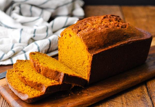 Horizontal side shot of the best pumpkin bread recipe on a wooden cutting board