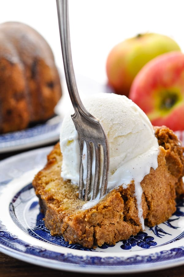 Close up shot of a fork digging into a slice of moist apple cake topped with a scoop of vanilla ice cream