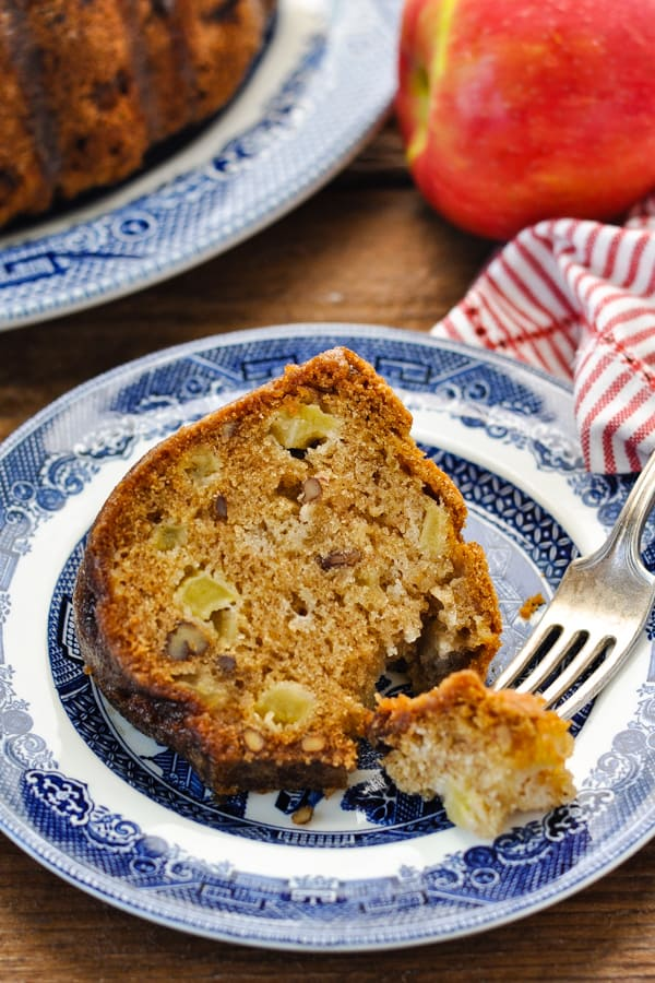 Fork taking a bite out of a slice of apple cake