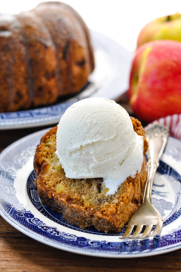 Front shot of old fashioned apple cake on a plate with vanilla ice cream on top