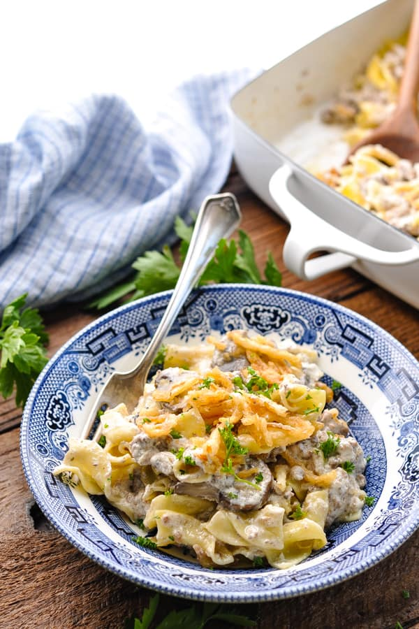 Front shot of a bowl of easy beef stroganoff casserole on a wooden table with parsley garnish