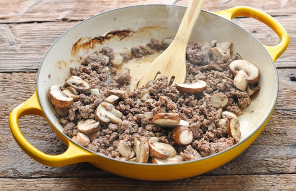 Cooked ground beef mushrooms and onions in a skillet